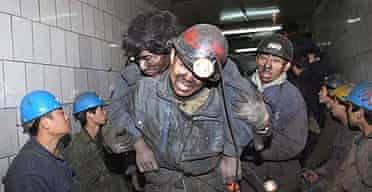 A miner is carried to safety following an explosion at a coal mine in north-east China