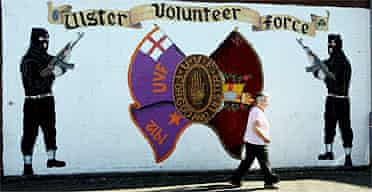 A woman passes a mural for the Ulster Voluteer Force in Belfast, Northern Ireland