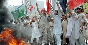 Activists of a Pakistani religious parties alliance chant slogans as they burn tires during an anti-government rally in Peshawar.  A general strike is being observed in Karachi and other major Pakistani cities. Photograph:  Mohammad/AP
