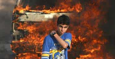 A young Palestinian in front of a burning vehicle in Gaza
