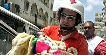 A Lebanese Red Cross worker carries a one-month-old Palestinian baby evacuated from Nahr al-Bared refugee camp in Tripoli