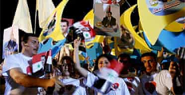Syrians wave their national flags during a patriotic gathering in support of Syrian president Bashar al-Assad in Damascus