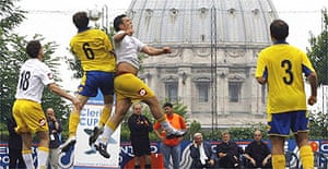 Redemptoris Mater football team players, wearing yellow and blue, challenge for the ball with Pontificia Universita' Lateranense players during the final of Clericus Cup tournament, at the St.Peter's parish recreation sports center in Rome