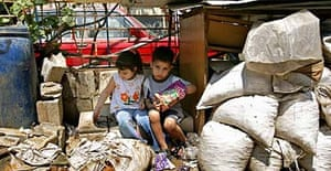 Palestinian refugee children, who fled the besieged camp of Nahr al-Bared in northern Lebanon, wait as their families collect aid donated by the UNRWA