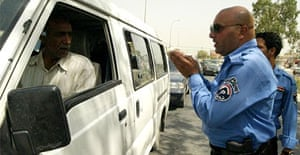 Iraqi police stop and check cars near the finance ministry in Baghdad, where five Britons were kidnapped