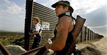 Minutemen in California look over the border wall for immigrants trying to cross into the US.