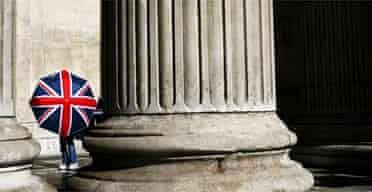 A girl holds an umbrella at St Pauls Cathedral in London