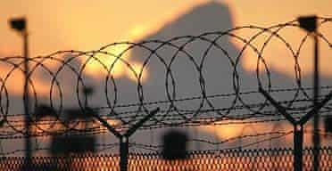 The sun rises over the razor-wired compound at Camp Delta, Guantanamo Bay.
