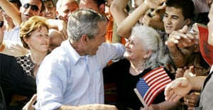 George Bush greets a women holding a US flag during a visit to Fushe Kruje in Albania