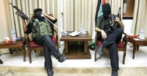 A Hamas fighter plays with the phone in the captured office of Palestinian president Mahmoud Abbas