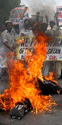 Religious students in Multan, Pakistan, burn effigies of the Queen and Salman Rushdie during protests against the awarding of the knighthood