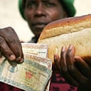 Zimbabwean woman holds bread and the money needed to buy it