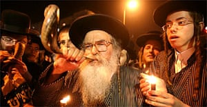 Ultra-Orthodox Jews blow the Shofar and hold black candles during protests in Jerusalem against the Gay Pride march