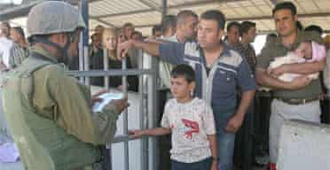 Palestinians wait for an Israeli soldier to check their identity cards at a checkpoint near the West Bank city of Nablus