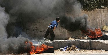 A boy in Gaza City stands among burning tires and looks at Israeli tanks in clashes with Hamas fighters.