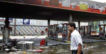 An Iranian man inspects the damage at his petrol station after it was attacked by angry demonstrators in Tehran