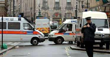 The junction of Coventry Street and Haymarket in central London is cordoned off as police officers investigate a 'viable explosive device'
