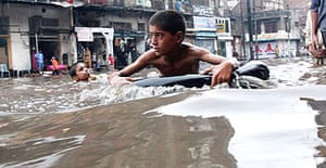 A Pakistani boy uses an inner tube as a flotation aid to cross a flooded street in Lahore