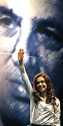 Cristina Fernández de Kirchner, standing in front of a poster of her husband
