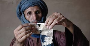 Fida ag Muhammad holds up the remains of a centuries old manuscript which has been eaten away by termites