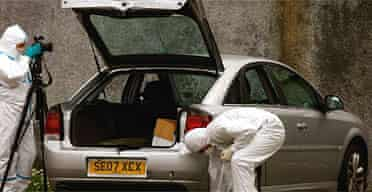 Forensic officers examine the Vauxhall Vectra left in the car park of the Forth Road mosque in Glasgow