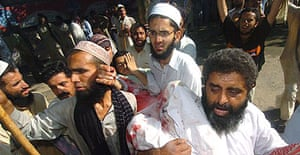 Radical students from Islamabad's Red Mosque carry an injured colleague following a gun battle with Pakistani security forces in which one soldier was killed