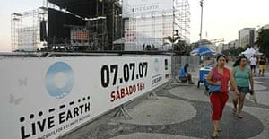 People walk past the stage where the Live Earth concert is due to be held