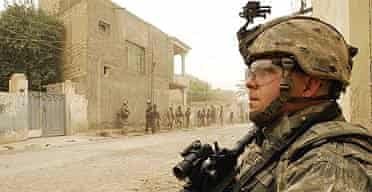 US and Iraqi soldiers stand on a street during a dawn raid on suspected al-Qaida members in Baquba, 35 miles north-east of Baghdad.