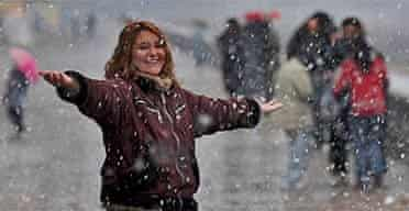 A woman enjoys the first major snowfall in nearly 90 years in Buenos Aires, Argentina