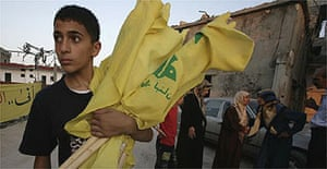 A boy carries Hizbullah flags