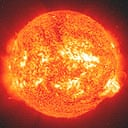 An ultraviolet image of the Sun shows a solar flare leaping out from an active sunspot