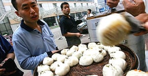 Customers buy steamed buns at a roadside stall in Beijing