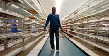 A Zimbabwean shopper walks through the empty shelves of a store in Harare