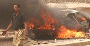 A man passes the scene of a bomb attack in Kirkuk, Iraq
