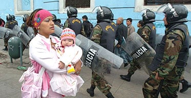 A Peruvian woman carries her child past a riot police patrol in central Lima