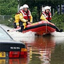 Emergency personnel pass an abandoned car in flood water in Tewkesbury