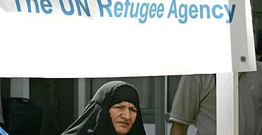 An Iraqi woman walks under a banner at the UNHCR office in Duma, Syria. One in seven Irais has been displaced by the war, according to Un figures.