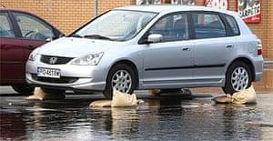 A car parked on sandbags to avoid flood damage in Botley, near Oxford