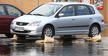 A car parked on sandbags to avoid flood damage in Botley, near Oxford