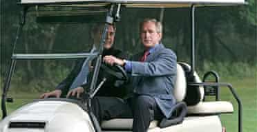 George Bush drives Gordon Brown in a golf cart after welcoming him to the presidential retreat at Camp David