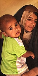 A mother and child sit in a tent at a camp for internally displaced people in Diwaniyah, 80 miles south of Baghdad, Iraq