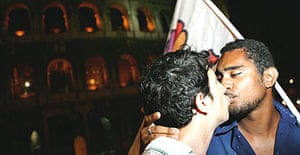 Italian gay right activists hold a public 'kiss-in' in front the Colosseum in Rome to protest against the arrest of two men caught by police kissing at the site