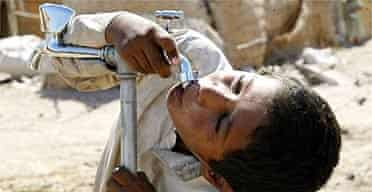 An Iraqi boy drinks from a tap at a camp for displaced people in Najaf