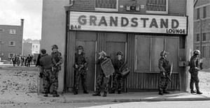 British soldiers hide behind a pub in Londonderry in 1971