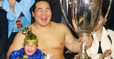Sumo champion Asashoryu celebrates winning the Emperor's Cup with his daughter in 2004