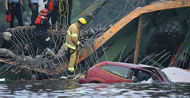 A rescue worker enters a car that plunged into the Mississippi after the bridge collapsed