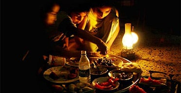 A family eats dinner by the light of an oil lamp in Sadr City in Baghdad, Iraq