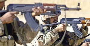 Iraqi soldiers train by shooting AK47 machine guns at a US marine base, near Baghdad.