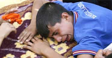 An Iraqi boy weeps over his father's coffin outside a hospital morgue after a military operation by US troops in Baghdad