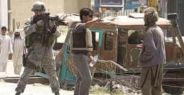 An American soldier aims his gun at an unarmed Afghan man near the site of a suicide bomb attack aimed at coalition troops, earlier this year.